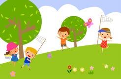 女孩和男孩捉住在绿色草坪的蝴蝶 免版税库存照片