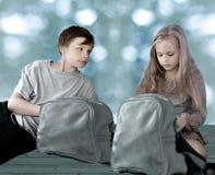 女孩和男孩有旅行的挑运坐地板以大窗口为背景 免版税库存照片