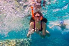 女孩和男孩游泳面具的在红海潜水在珊瑚礁附近 库存照片