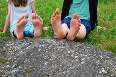 女孩和男孩的赤脚岩石的 库存图片