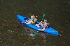 女孩和男孩皮船的在河乌尔特河在La罗氏enArdenne,比利时附近 免版税库存图片