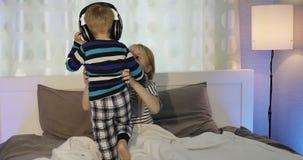 女孩和男孩耳机的在床上说谎并且听到音乐 股票视频