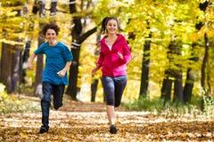 女孩和男孩赛跑,跳跃在公园 库存图片