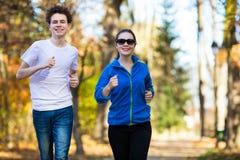 女孩和男孩赛跑,跳跃在公园 免版税库存图片