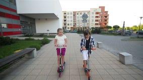 女孩和男孩骑马户外反撞力滑行车 使用在街道上的愉快的逗人喜爱的孩子学会平衡在反撞力委员会 股票录像