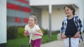 女孩和男孩骑马户外反撞力滑行车 使用在街道上的愉快的逗人喜爱的孩子学会平衡在反撞力委员会 影视素材