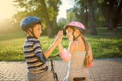 女孩和男孩骑马自行车在公园 库存照片