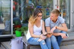 女孩和男孩结合坐餐馆的门廊,谈话 库存图片