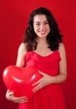 女孩和红色心形的气球 免版税库存照片