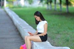 女孩和谈话坐电话在公园 库存照片