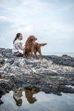 女孩和金毛猎犬 库存照片