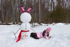 女孩和雪人 免版税库存图片