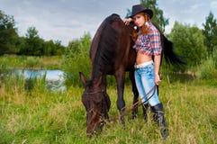 女孩和马在池塘附近 库存照片