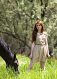 女孩和马在草甸 免版税库存照片
