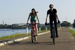 女孩和年轻人在一辆自行车乘坐在城市 库存图片