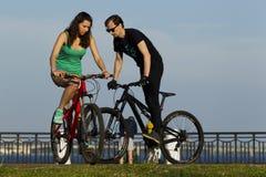 女孩和年轻人在一辆自行车乘坐在城市 库存照片