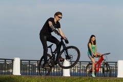 女孩和年轻人在一辆自行车乘坐在城市 免版税库存图片