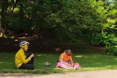 女孩和年轻男孩运动服的和体育盔甲坐关于 免版税库存照片