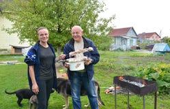 女孩和年长人准备从鹌鹑的一串烤肉串在火盆 免版税库存图片