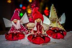 女孩和Agels在帽子在雪,在说谎的星后 库存图片
