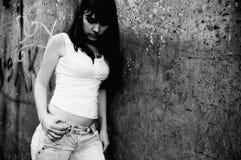 女孩哀伤的常设墙壁年轻人 免版税库存照片