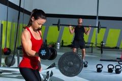 女孩哑铃和人举重棒锻炼 免版税库存图片