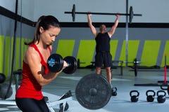 女孩哑铃和人举重棒锻炼 免版税库存照片