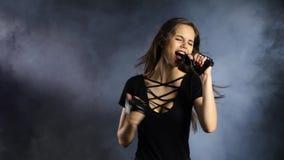 女孩唱摇摆物歌曲,她精力充沛和性感 黑烟背景 股票视频