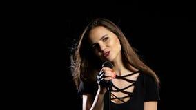 女孩唱摇摆物歌曲,她精力充沛和性感 黑色背景 影视素材