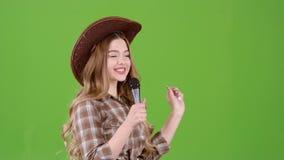 女孩唱歌入一个减速火箭的乡村音乐话筒 绿色屏幕 侧视图 股票视频