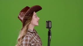 女孩唱歌入一个减速火箭的乡村音乐话筒 绿色屏幕 慢的行动 侧视图 影视素材