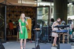 女孩唱歌到话筒朋友戏剧合成器 免版税图库摄影