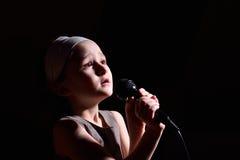 女孩唱歌的一点 库存照片