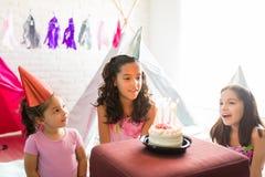 女孩唱歌看蛋糕的朋友的生日歌曲在同水准期间 免版税库存照片