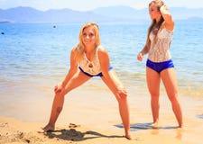 女孩啦啦队员在膝盖的姿势手其他在沙子待命 库存照片