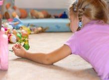 女孩喂养鹦鹉新鲜的草 免版税图库摄影