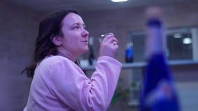 女孩喝从一块玻璃的酒,象伏特加酒 一个党 在前景瓶 股票录像