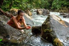 女孩喝从山小河的水 免版税库存照片