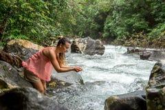 女孩喝从山小河的水 库存照片