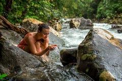 女孩喝从山小河的水 库存图片