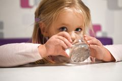 女孩喝从玻璃的水在桌上 库存图片