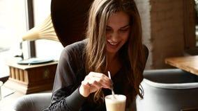 女孩喝在咖啡馆的咖啡 妇女笑 股票录像