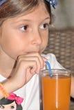 女孩喝汁液 免版税库存图片