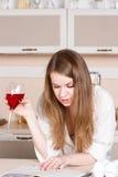 女孩喝红葡萄酒和读一本书的白人的衬衣在厨房里 免版税图库摄影