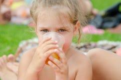 女孩喝从塑料一次性杯子的汁液在野餐 免版税库存照片
