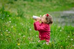 女孩喝从热水瓶的水 杯子热水瓶,春天草,卷发,室外休闲,健康 免版税库存照片