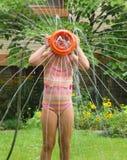 女孩喷水隆头 免版税库存照片