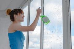 女孩喷洒洗涤的窗口的液体在肮脏的玻璃 库存图片