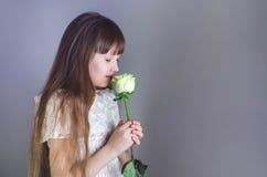 女孩嗅到玫瑰 图库摄影