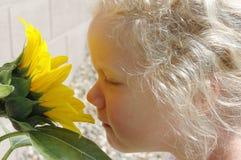 女孩嗅到的向日葵年轻人 免版税库存图片